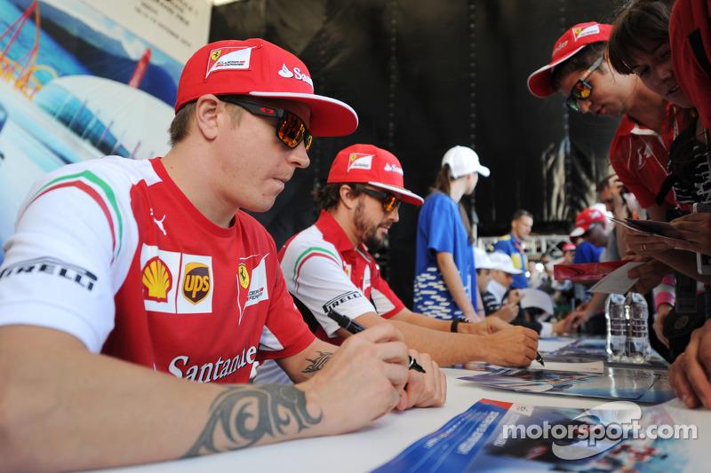 (L to R): Kimi Raikkonen, Ferrari and team mate Fernando Alonso, Ferrari sign autographs for the fan