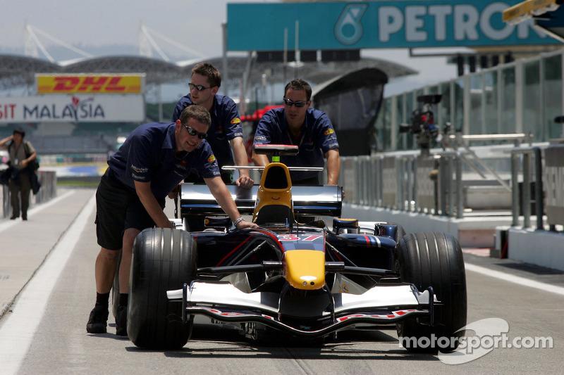 Los miembros del equipo Red Bull empujan el coche