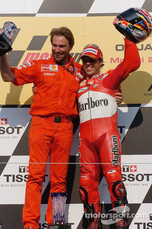 Podio: ganador de la carrera Loris Capirossi celebra con Livio Suppo