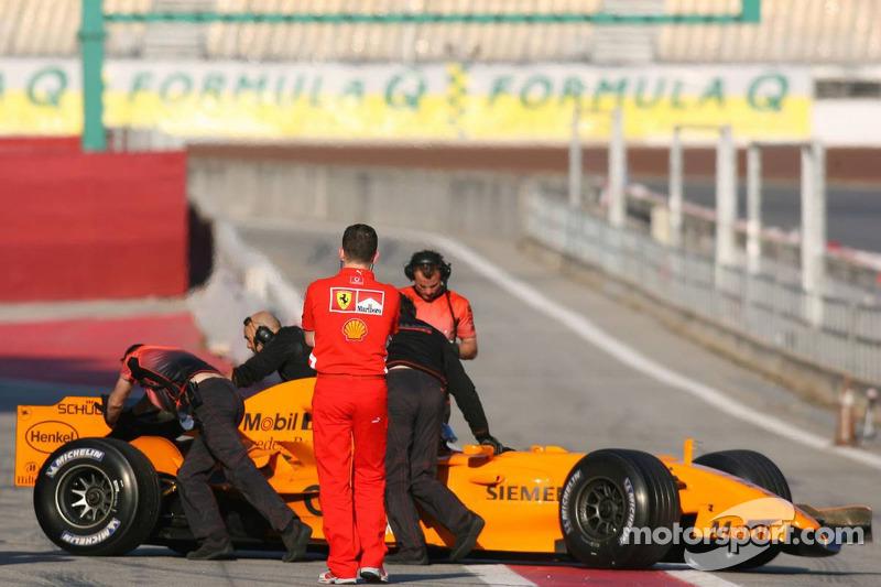 Ferrari crew members watch the new McLaren MP4-21 of Gary Paffett