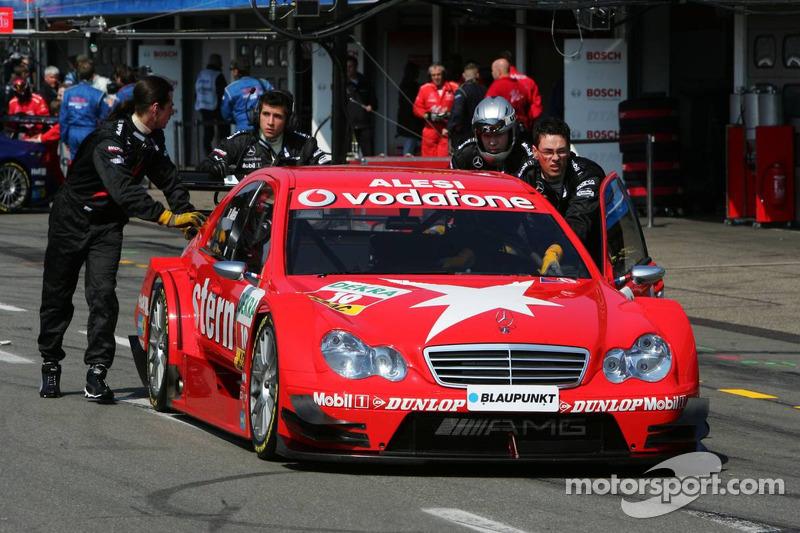 Mécaniciens poussent la voiture de Jean Alesi dans le parc fermé après qu'il a échoué à se qualifié dans le Top 16 en qualifications