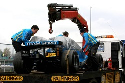 Fernando Alonso's car is returned to the pits after stopping on circuit