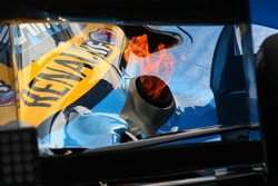 Fire comes out of the exhaust of Fernando Alonso as he returns to the pits