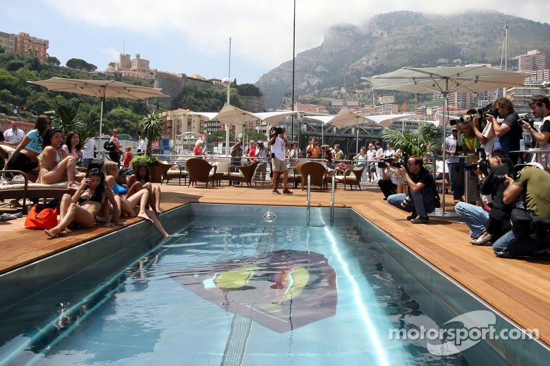 Des jeunes femmes Formule 1 avec des photographes dans la piscine Superman