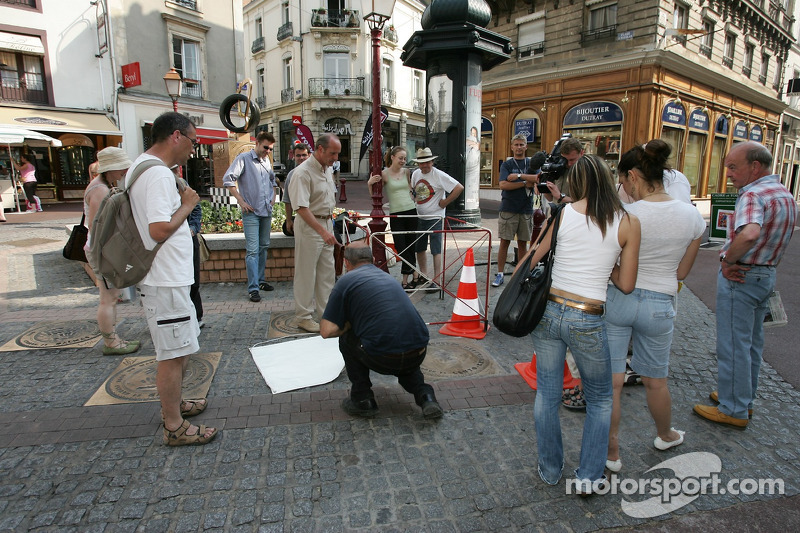 Découverte de la plaque des vainqueurs des 24 Heures du Mans 2005: des spectateurs regardent un homme prépare l'