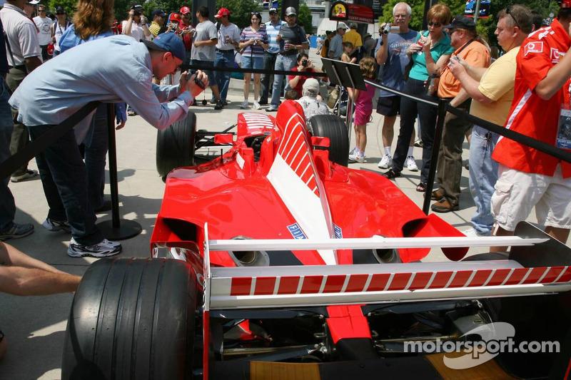 Des fans sur le circuit prennent des photos d'une voiture Ferrari F1