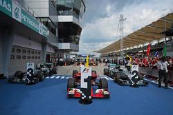De Ferrari SF15-T van racewinnaar Sebastian Vettel, Ferrari, in parc ferme, geflankeerd door de Merc