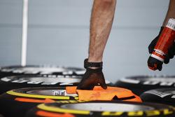 Un mecánico pinta marcas direccionales en los neumáticos Pirelli