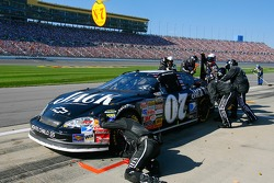 Crew members for Clint Bowyer work on the car during a pit stop after crashing