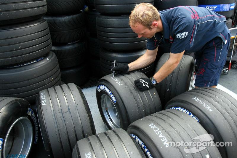 Un membre de Red Bull Racing marque des pneus Michelin