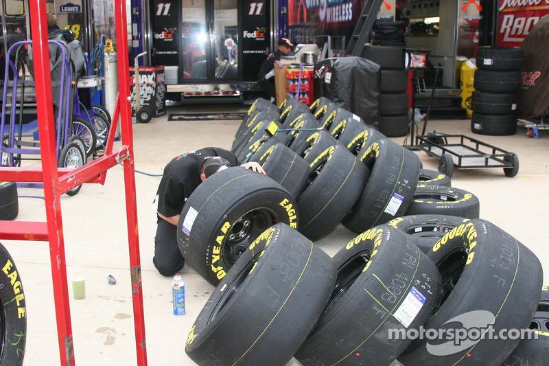 Des membres de l'équipe travaillent sur les pneus avant la course