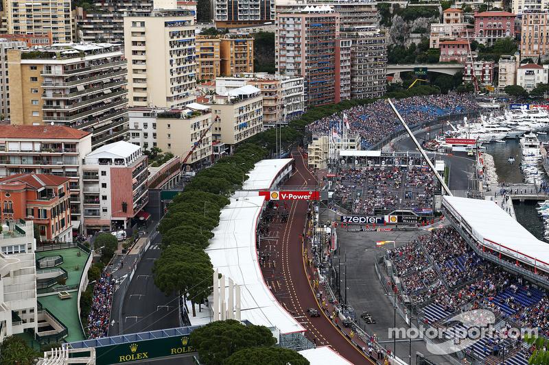 Romain Grosjean, Lotus F1 E23 in the pits and Pastor Maldonado, Lotus F1 E23 on the circuit