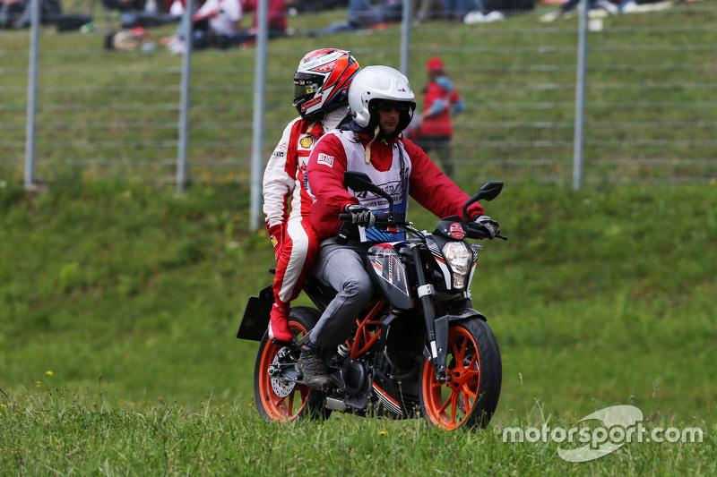 Race retiree Kimi Raikkonen, Ferrari returns to the pits on the back of a motorbike