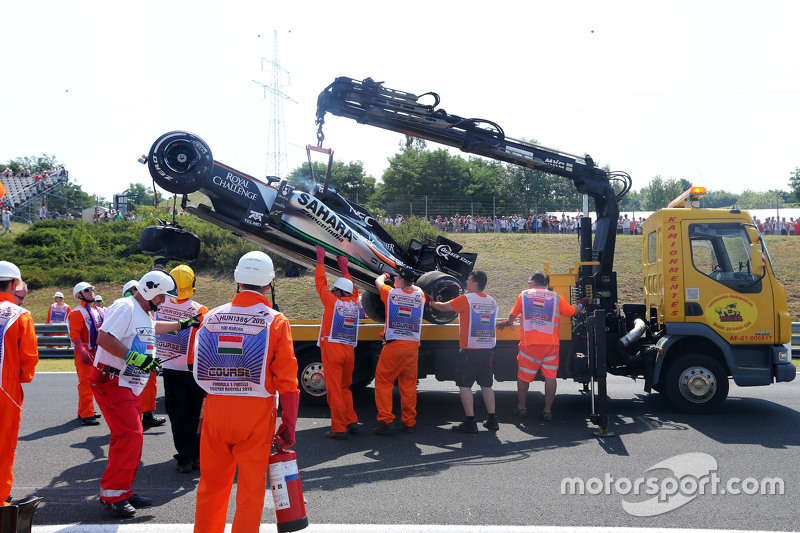 Safety crews tend to the crashed car of Sergio Perez, Sahara Force India F2