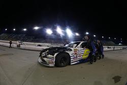 Roush Fenway Racing mechanics push the damaged Ford of Darrell Wallace Jr.