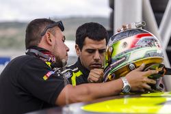 Manolín Gutiérrez y un miembro de su equipo revisan su casco