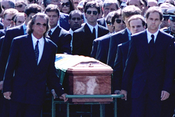 Emerson Fittipaldi, Jackie Stewart, Johnny Herbert, Derek Warwick, Gerhard Berger, Rubens Barrichello, Thierry Boutsen, Alain Prost et Damon Hill aident à diriger le cercueil d'Ayrton Senna pendant les funérailles