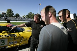GT pole winner Jan Magnussen Corvette Racing team members share a laugh while looking at the light damage on his car