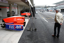 Bernie Ecclestone, walks past the Manor Marussia F1 Team pit garage