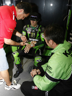 Dean Miller tapes Anthony West's injuries watched by Kawasaki Competition Manager Michael Bartholemy