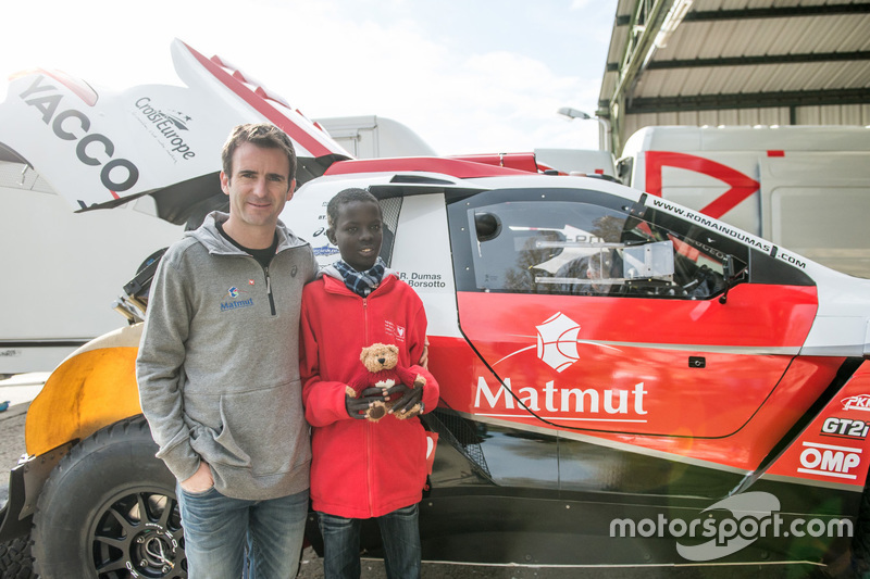 Romain Dumas and Samba, a Senegalese boy who was saved thanks to Mécénat Chirurgie Cardiaque, with t