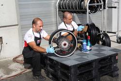 Crew members clean bike wheels
