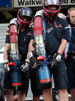 Les membres d'équipage de Red Bull Racing avec un injecteur de carburant pendant un entraînement aux stands