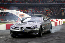 Lewis Hamilton waves to the crowd as he gives his father Anthony a ride in the McLaren Mercedes SLR