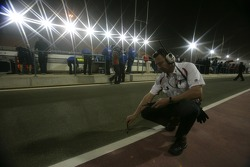 A Bridgestone Tyre engineer checks the track temperature