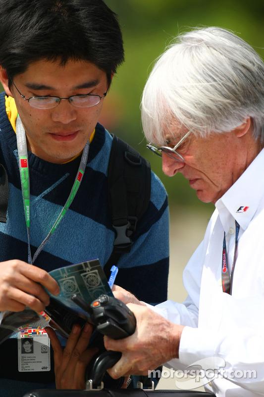 Bernie Ecclestone, President en CEO Formula One Management deelt handtekeningen uit