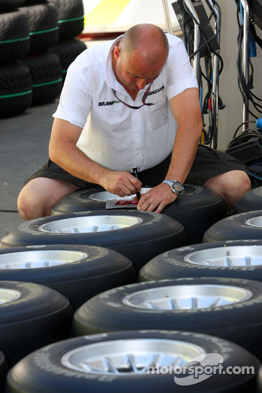 A Brawn GP mechanic working on the tyres