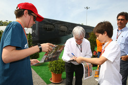 Bernie Ecclestone, President and CEO of Formula One Management signing autographs