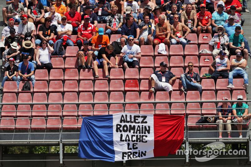 Romain Grosjean, banner de Haas F1 Team con fans en la tribuna
