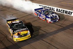 Race winner Kevin Harvick does a burnout as Ron Hornaday celebrates with his own burnout after clinching the NASCAR Camping World Truck Series 2009 title with a fourth place finish