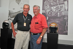 Ned Jarrett and Bobby Allison pose in front of their wall-sized photos from years ago