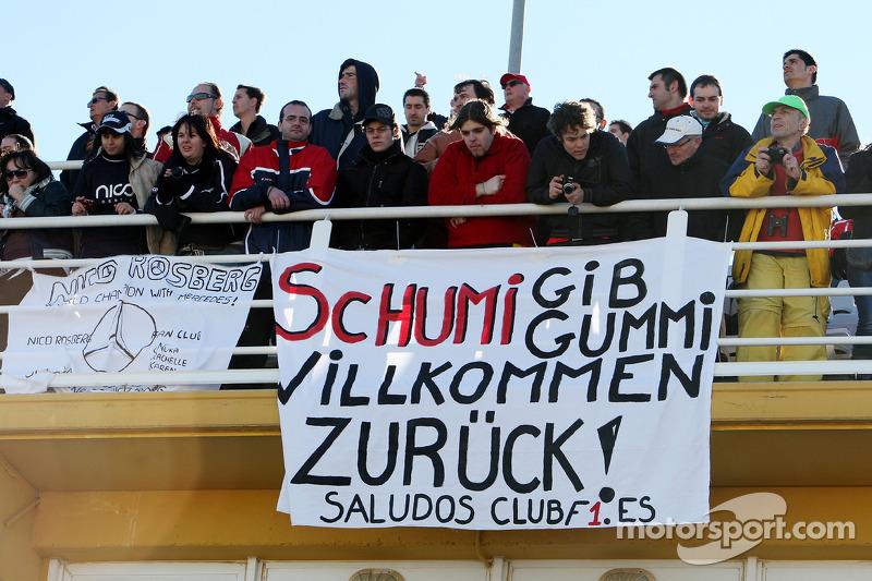 Aficionados observan la acción con una pancarta para Michael Schumacher, Mercedes GP