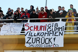 Fans watch the action with a banner for Michael Schumacher, Mercedes GP