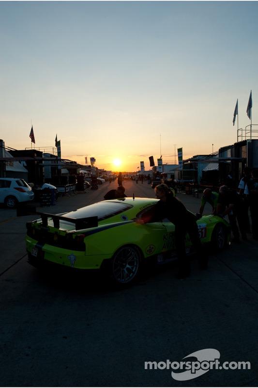 Krohn Racing crew duwt hun auto tijdens zonsondergang de paddock in