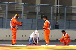 Marshals work on the kerbs after GP2 qualifying is postponed